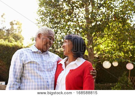 Senior black couple in their garden looking at each other