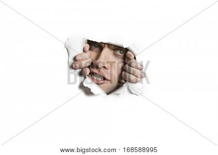 Portrait of a aggressive mid adult man peeking from ripped white paper hole