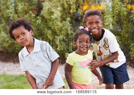 Three African American kids in a garden looking to camera