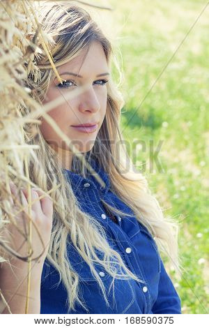 Thoughtful young blonde woman outdoors looking. In a field near a bale of hay. Intense sun lights.
