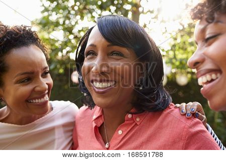 Black mother and two adult daughters in garden, close up