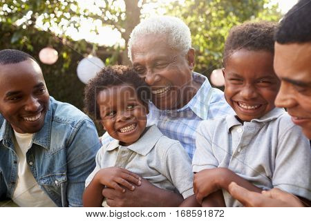 Multi generation male family members gathered in a garden
