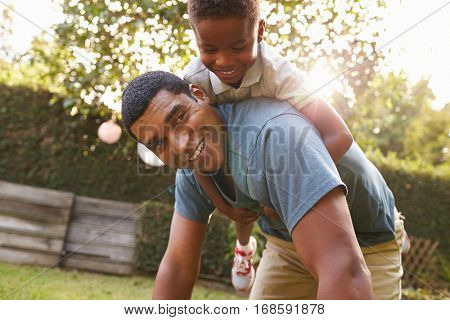 Young black boy playing on dadâ??s back in a garden, low angle