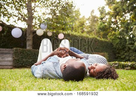 Young black couple lying on grass looking at each other