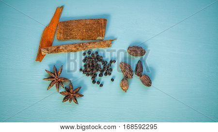 Overhead view of spices on blue background.