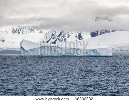 Low clouds and icebergs surrounding the mountainous coastline of Anvers Island Neumayer Channel Antarctica