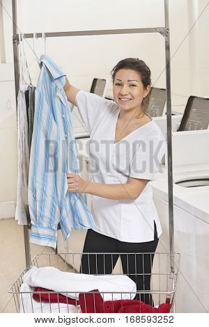 Portrait of a happy young woman hanging shirt in front of washing machines in Laundromat