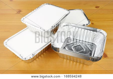 Aluminium foil take away trays on a wooden background