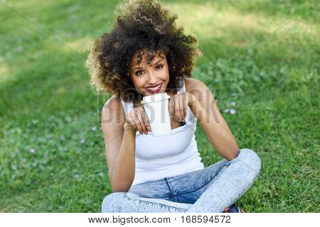 Woman With Afro Hairstyle Drinking Coffee In Park