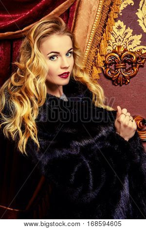 Charming woman with beautiful blonde hair wearing mink fur coat. Winter fashion. Luxurious classic vintage interior.