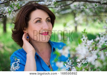 Close Up Portrait Of Middle Aged Woman Posing In Cherry Garden