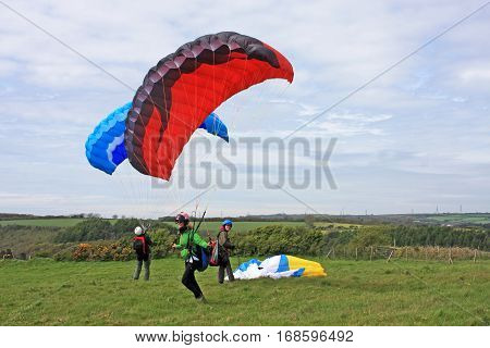 Paragliders preparing to launch their paraglide wings