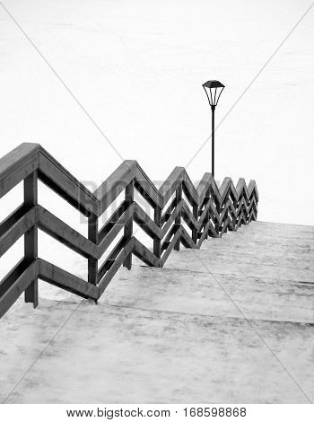 Long frozen wooden staircase with handrails leading down, post lantern street lighting and endless snow surface black and white photo vertical view