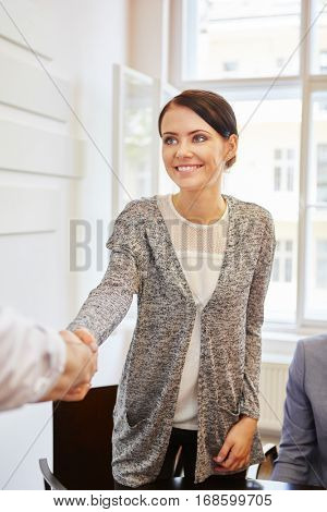 Young woman shaking hands in her start-up