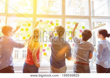 Students putting sticky notes on window for planning analysis