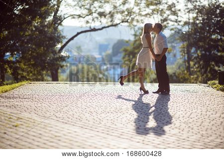 happy young couple kissing outdoor in the summer park