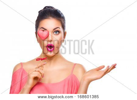 Beauty surprised Young fashion model Girl with Valentine Heart shaped cookie in hand. Love. Beautiful young woman pointing hand, advertising gesture. Valentines Day gift. Isolated on white background.