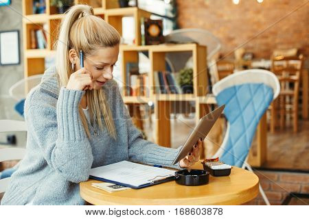 Young woman taking notes and holding tablet in cafe