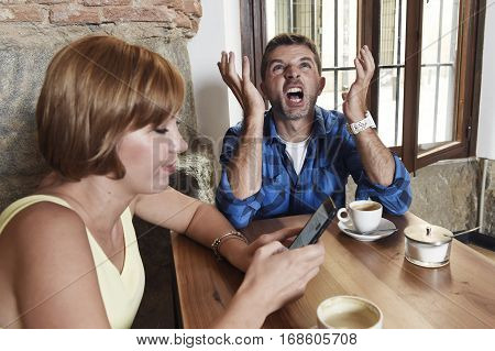 young American couple at coffee shop with internet and mobile phone addict woman ignoring bored desperate and frustrated man boyfriend or husband in relationship problem and addiction concept