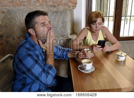 young American couple at coffee shop with internet and mobile phone addict woman ignoring bored sad and frustrated man boyfriend or husband yawning in relationship problem addiction concept
