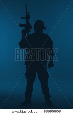 United states Marine Corps special operations command Marsoc raider with weapon. Silhouette of of Marine Special Operator blue background full body