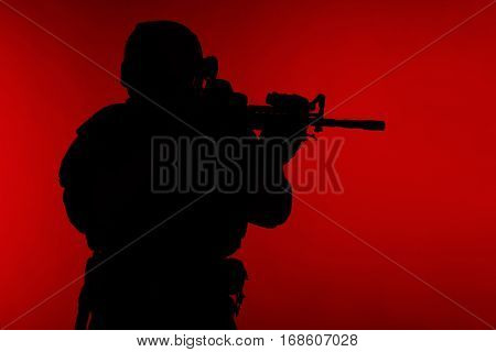 United states Marine Corps special operations command Marsoc raider with weapon aiming a gun. Silhouette of Marine Special Operator red background