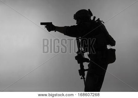 United states Marine Corps special operations command Marsoc raider with weapon aiming pistol. Silhouette of Marine Special Operator gray background