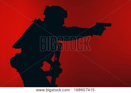 United states Marine Corps special operations command Marsoc raider with weapon aiming pistol. Silhouette of Marine Special Operator red background