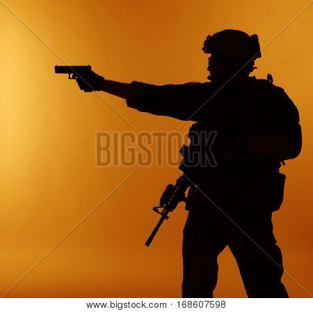 United states Marine Corps special operations command Marsoc raider with weapon aiming pistol. Silhouette of Marine Special Operator orange background