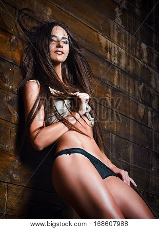Fashion shot: a sexy young woman in panties and shirt stands at the wood wall