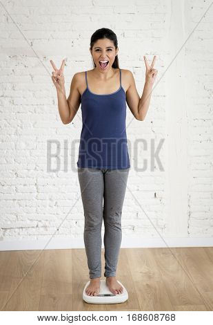 young attractive slim latin woman or teenager girl checking weight on scale smiling happy and satisfied in weight loss success and diet concept