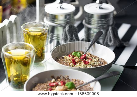 Chocolatiers breakfast for two person with oatmeal, puffed rice, cereals , dried strawberries and  tea prepared in a white bowl.
