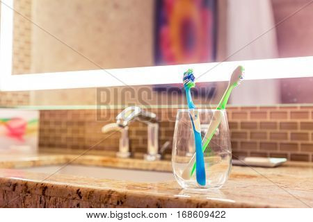 Toothbrushes in a glass on counter.