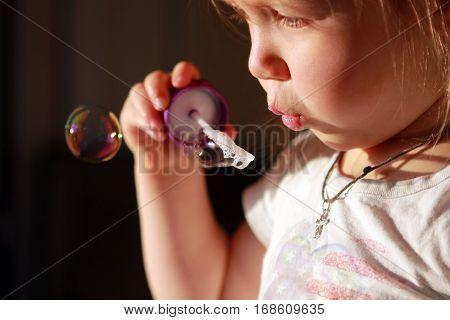 Portrait little cheerful inflates soap bubbles .