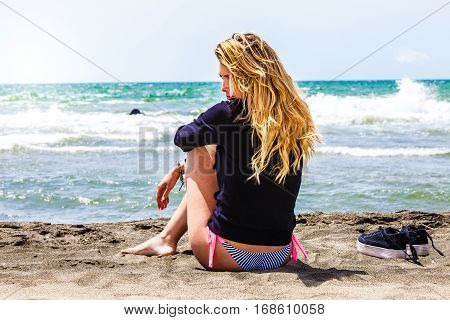 Lonely girl sitting at the beach with sea. Thoughtful and loving. Young girl sitting on the beach relaxing. In the background the waves of the Mediterranean Sea. Beside her shoes.