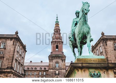 Christiansborg palace and King Christian IX statue in Copenhagen, Denmark. Famous landmark of danish capital. The seat of parliament on Slotsholmen.