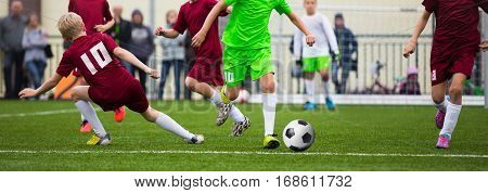 Children Soccer Football Players. Footballers Kicking Football Match Game on the Grass. Young Soccer Players Running After the Ball. Horizontal Youth Sports Background