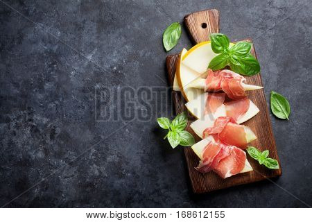 Fresh melon with prosciutto and basil. Antipasti. Top view on dark stone table with copy space for your text