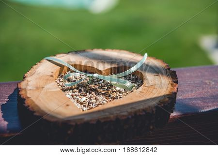 Wooden holder with satine link for wedding rings. Close up view