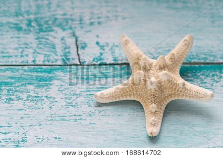 Starfish on blue scratched old wooden background