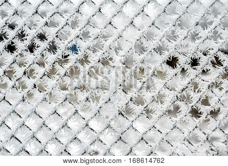 Chain link fence covered by frost crystals, cold winter weather outdoors