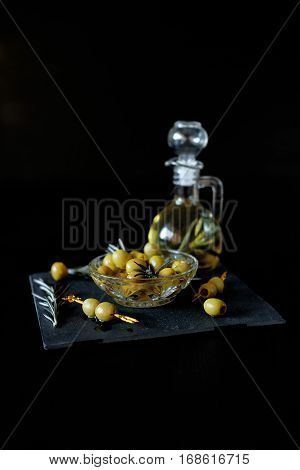 Green olives on picks with rosemary and olive oil in a bootle with herbs