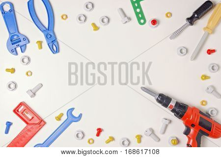 Toy construction tools from kids tool kit as frame on white background. Top view. Flat lay. Copy space text