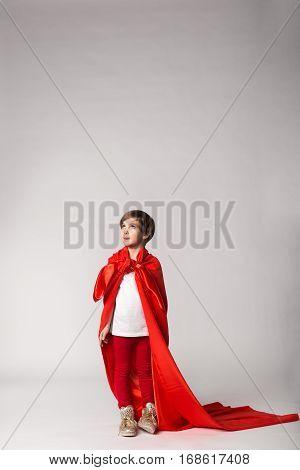 Super Hero Girl In Red Cape Posing In Studio.