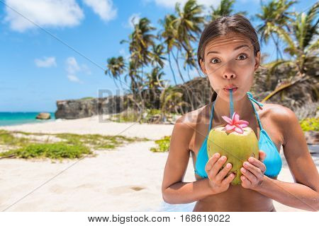 Funny girl having fun drinking coconut water on beach. Cute Asian woman doing goofy face sipping with straw on natural fruit for healthy hydration drink during tropical travel destination holiday.