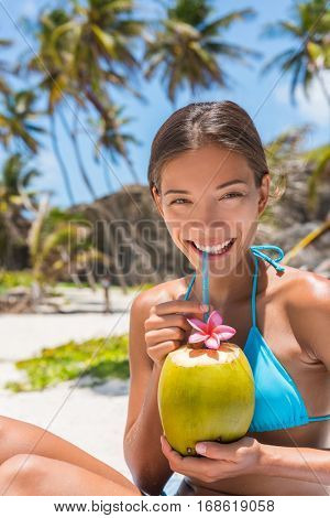 Beautiful Asian bikini woman drinking fresh coconut water directly from fruit with straw on beach. Multiracial girl smiling at camera portrait with perfect teeth sipping on hydration juice food.