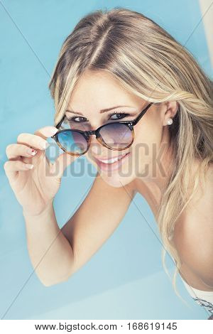 Beautiful smiling blonde hair girl with sunglasses in the pool. A pleasant blonde woman holds in one hand her sunglasses showing eyes, beautiful smile. Behind her water from a clean summer pool.