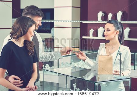 Couple of handsome man and attractive brunette woman paying for purchase at jewelry store by golden card. Female seller smiling to buyers, packing purchase in paper bag and taking for payment card.