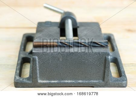 The vise to clamp on a wooden desktop environment tools.