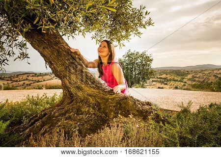 View Of A Girl Standing Under The Old Olive Tree